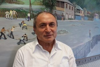 שלום שי // בעלים ומנכל חברת דונה על רקע ציור בית ילדותו בגיאורגיה